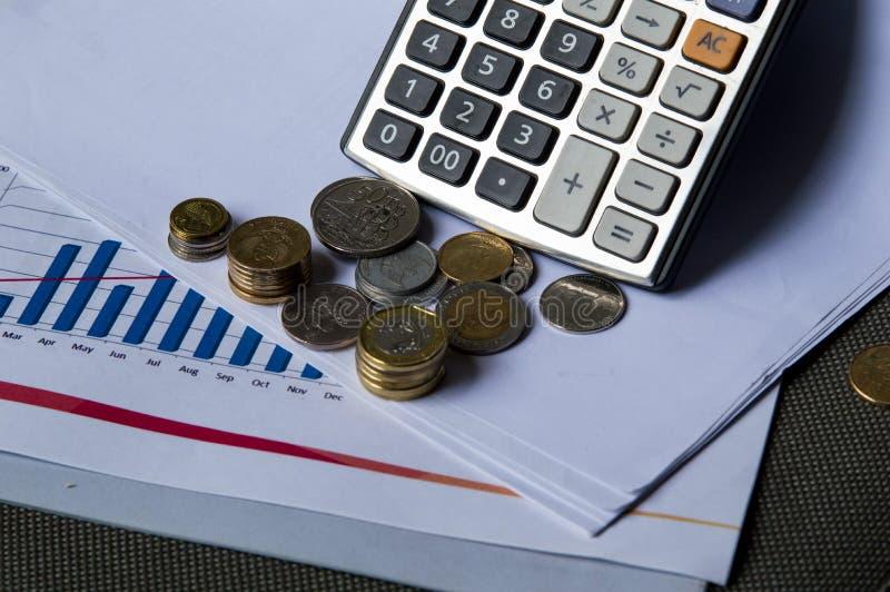 Soldi e calcolatore della moneta sulla tavola immagini stock