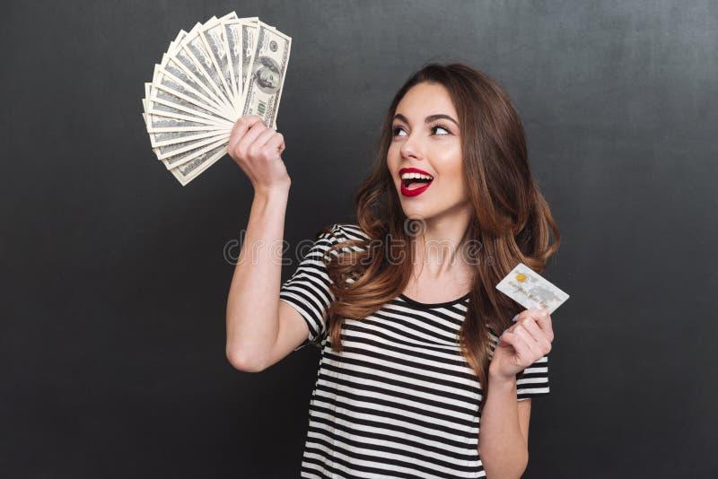Soldi e carta di debito felici della tenuta della giovane signora in mani fotografie stock