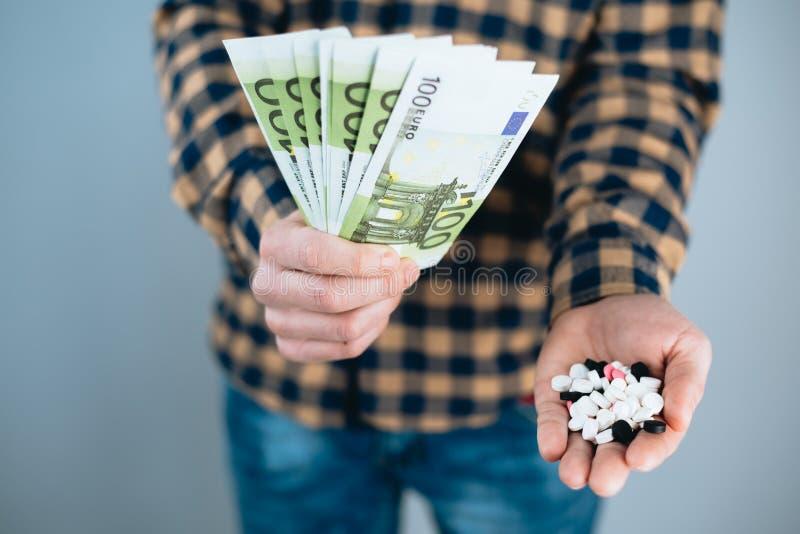 Soldi e pillole a disposizione, spendendo troppi soldi sulle droghe Il concetto di dipendenza fotografia stock libera da diritti