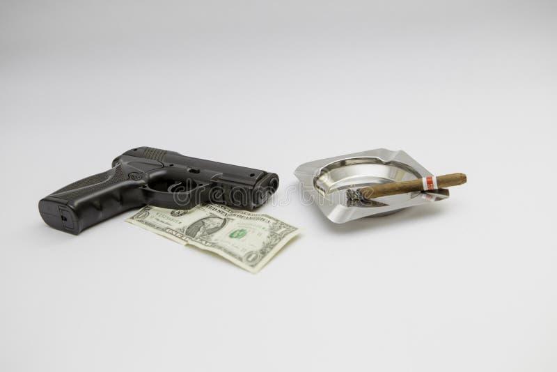 Soldi e sigaro della pistola separati ai precedenti bianchi fotografie stock libere da diritti
