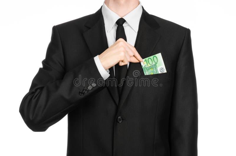 Soldi e tema di affari: un uomo in un vestito nero che giudica un euro della banconota 100 isolato su un fondo bianco in studio immagini stock