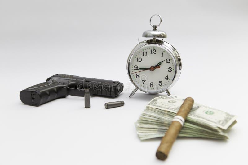 Soldi ed orologio della pistola ai precedenti bianchi fotografie stock