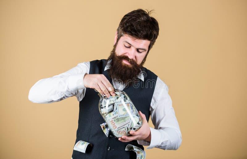 Soldi nascondentesi per uso futuro Uomo barbuto che investe soldi dal barattolo di vetro per i profitti futuri Uomo d'affari che  fotografie stock libere da diritti