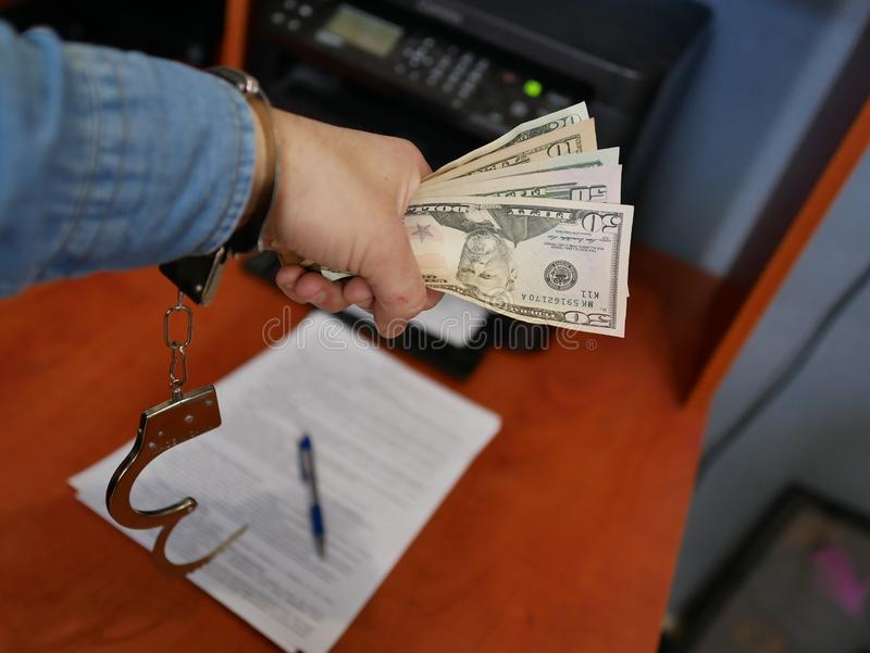 Soldi nelle mani di un bandito Crimine finanziario immagine stock