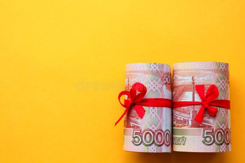 Soldi russi 5000 rubli torte in un tubo e legate con un nastro, su un fondo colorato immagine stock