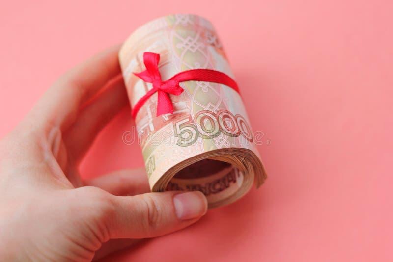 Soldi russi 5000 rubli torte in un tubo e legate con un nastro, su un fondo colorato fotografia stock libera da diritti