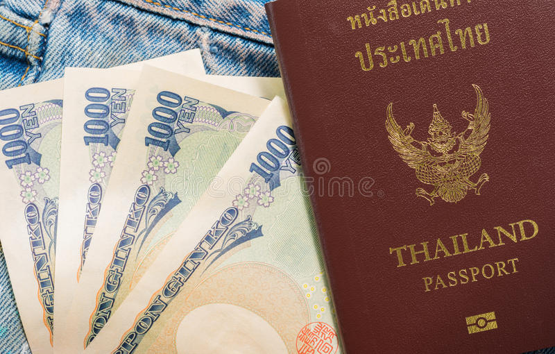 Soldi tailandesi di Yen e del passaporto in tasche delle blue jeans fotografie stock