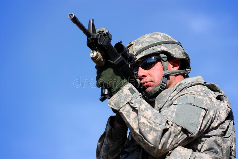 A soldier aiming. With his weapon isolated on a blue sky background royalty free stock image