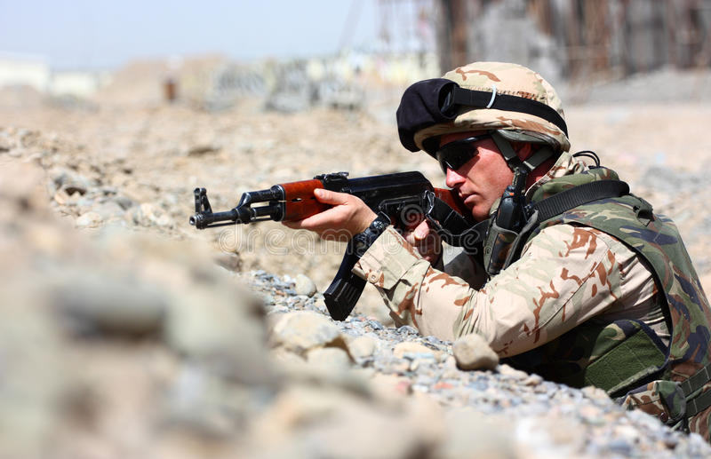 A soldier aiming. A soldier with helmet and desert camouflage uniform aiming his automatic rifle (AK47) using tranche for cover stock images