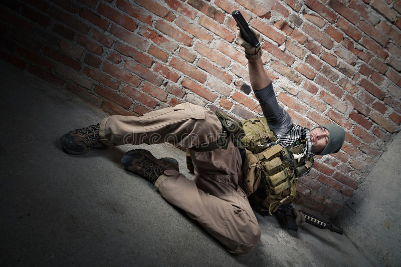 Soldier aiming pistol. On bricks background royalty free stock photos