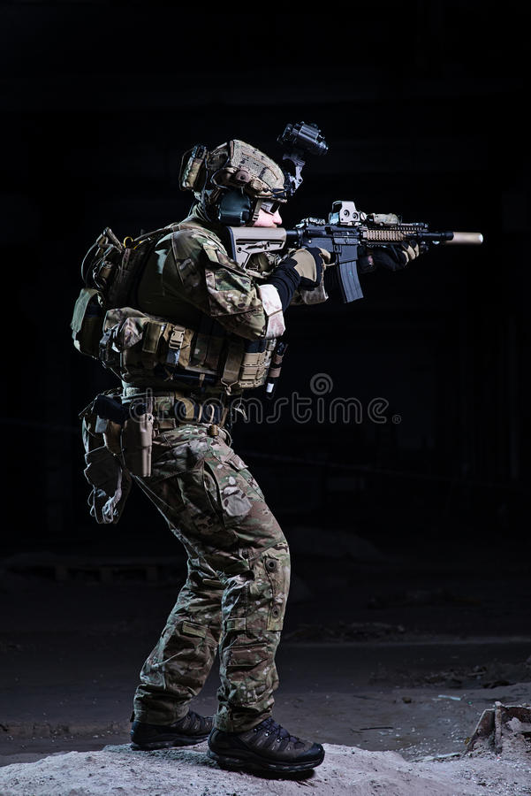 Soldier aiming from rifle on dark background royalty free stock photography