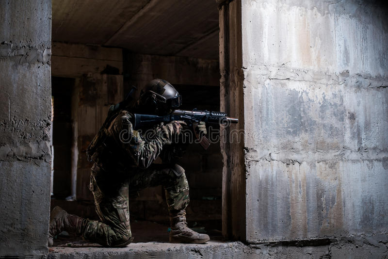 Soldier aiming a rifle in ruins royalty free stock image