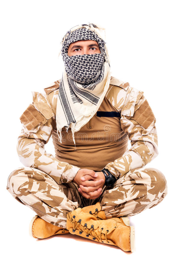 Soldier with arabian scarf covering his face, sitting cross- l stock image