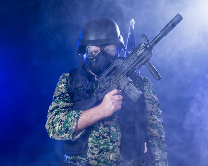 Soldier holding assault rifle in smoky haze royalty free stock photo