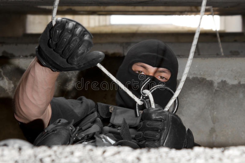 Soldier in black mask dealing with rope stock photo