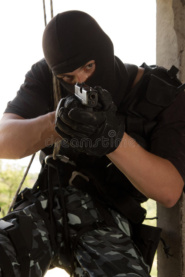 Soldier in black mask entering through the window royalty free stock images