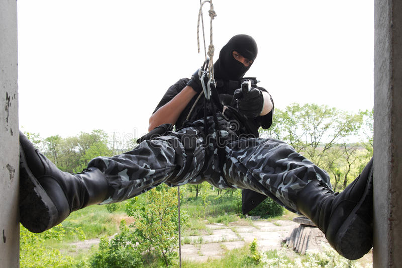 Soldier In Black Mask Hanging On Rope Royalty Free Stock Image