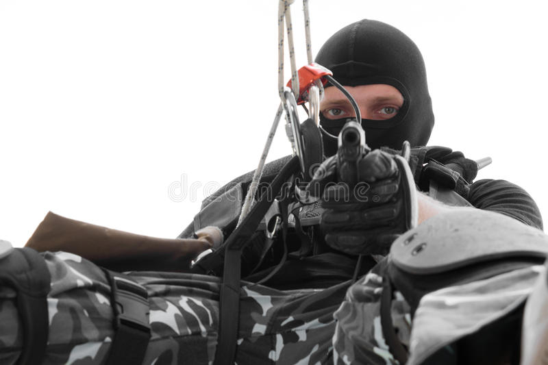 Soldier in black mask hanging on rope with pistol stock photo