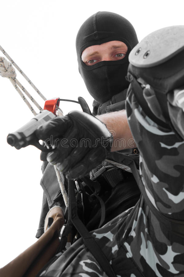 Soldier in black mask hanging on rope with pistol stock images