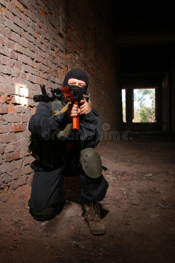Soldier in black mask targeting with a gun stock photos