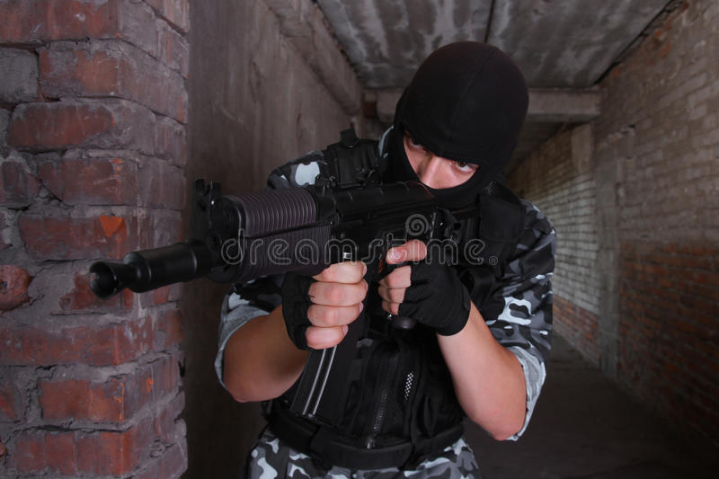 Soldier in black mask targeting with a gun royalty free stock photography