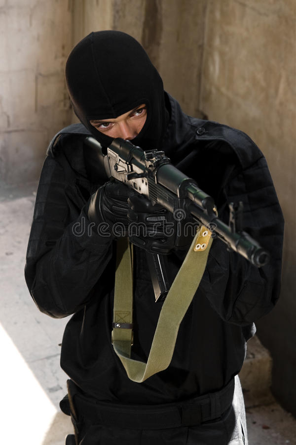 Soldier in black uniform with rifle stock image