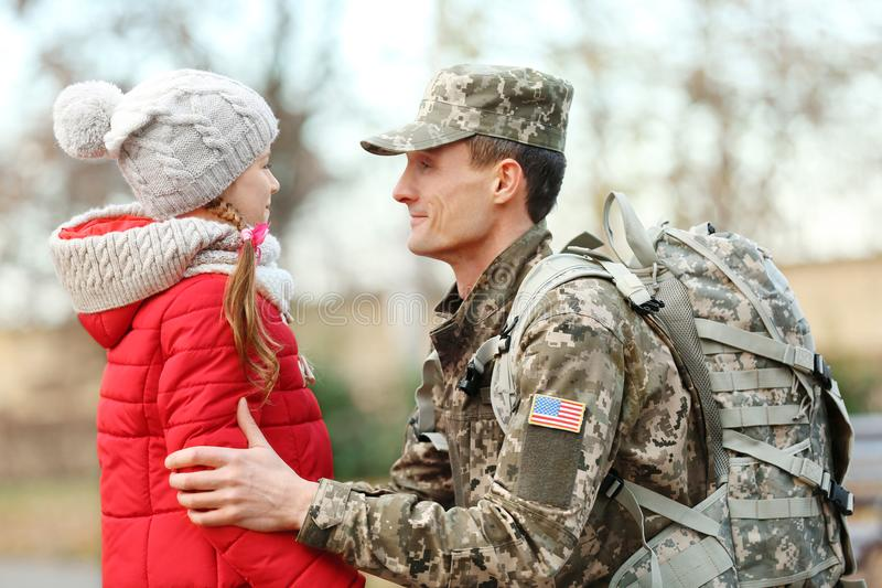 Soldier in camouflage with his daughter royalty free stock photo