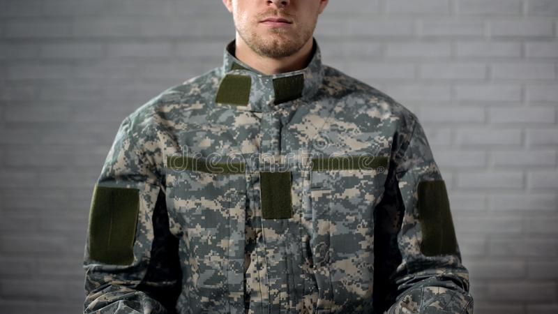 Soldier in camouflage sitting against white wall, military service, template. Stock photo royalty free stock image
