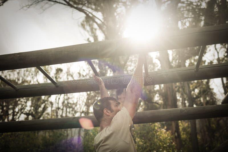 Soldier climbing monkey bars stock photos