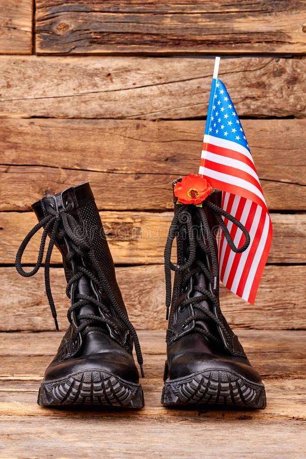 Soldier combat boots with us flag and red poppy. Wooden desk background stock images