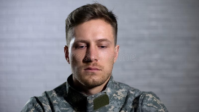 Soldier crying and looking down, remembering dead fellows and feeling hopeless stock photos