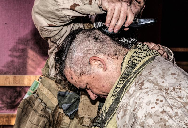 Soldier cuts comrades hair with trimmer or clipper. Soldier cuts comrades hair with trimmer. United States marine shaving friends head with clipper in combat stock images