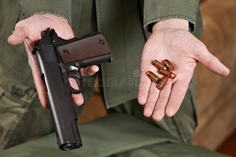 Soldier demonstrates Colt pistol and cartridges to it stock photo
