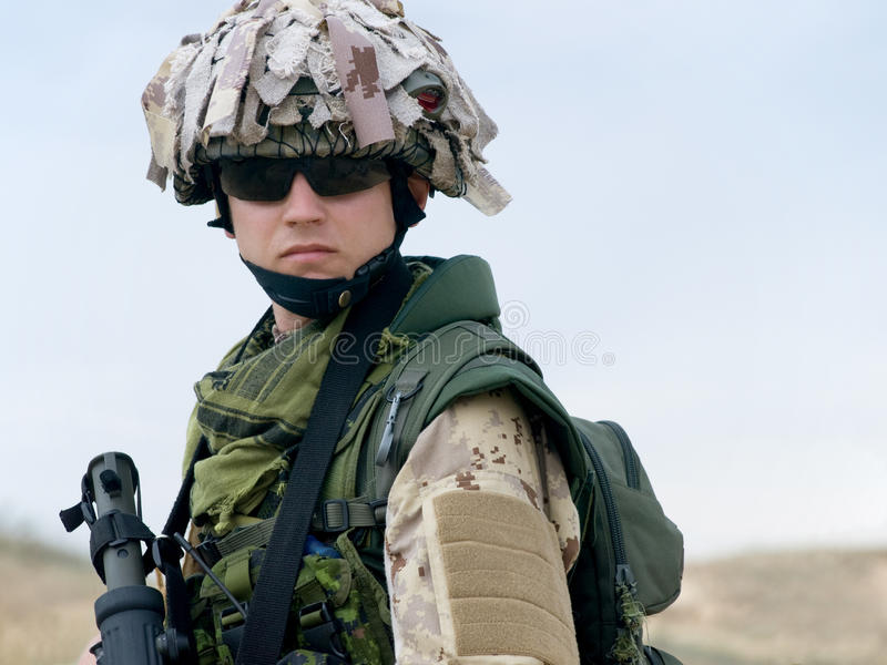 Soldier in desert uniform. Holding his rifle royalty free stock image