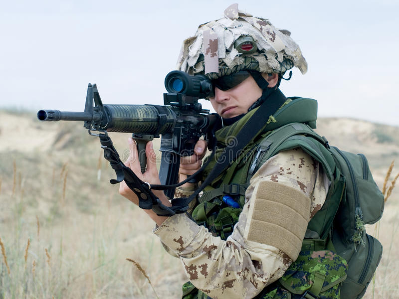 Soldier in desert uniform. Aiming his rifle royalty free stock photos