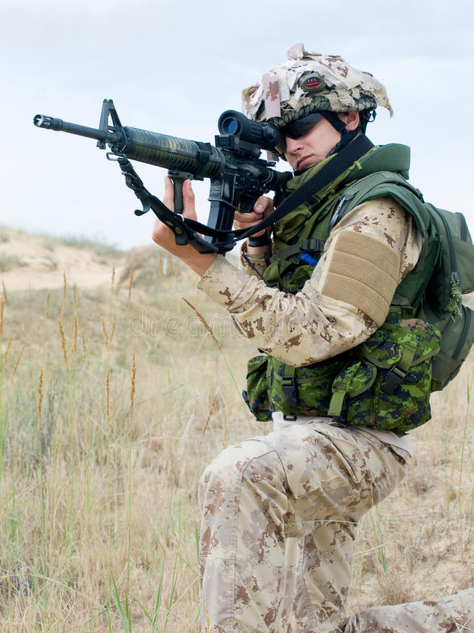 Soldier in desert uniform. Aiming his rifle stock photo