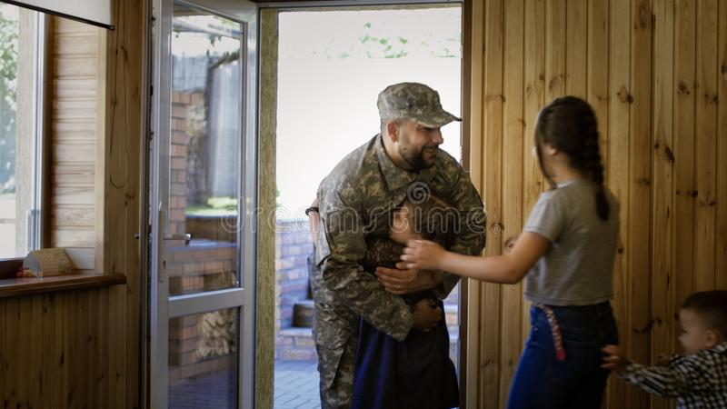 Soldier entering home with happy family stock photo