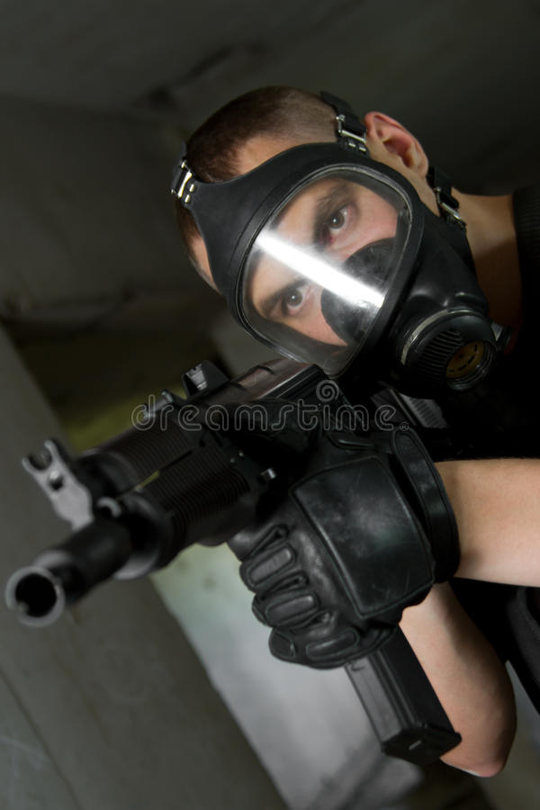 Soldier in gas mask targeting with AK-47 rifle stock images