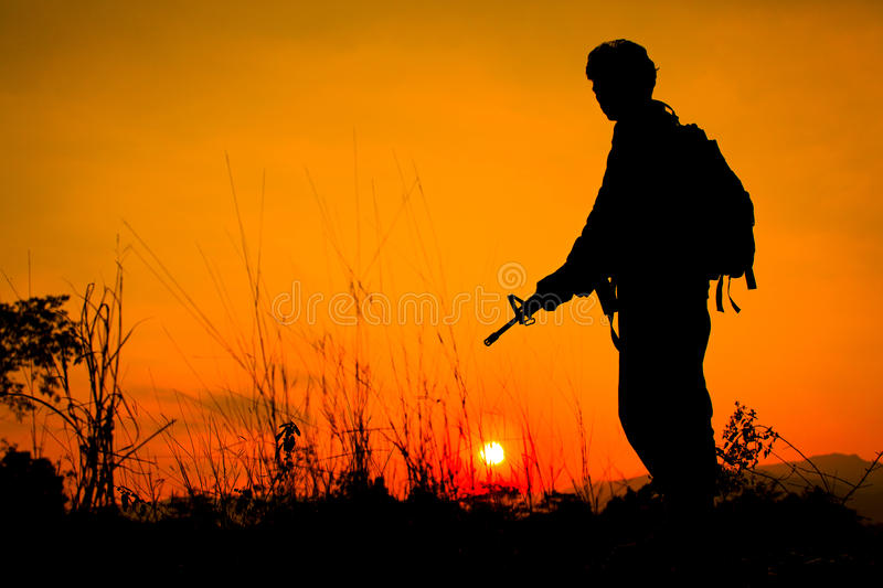 Soldier and gun in silhouette shot royalty free stock photography