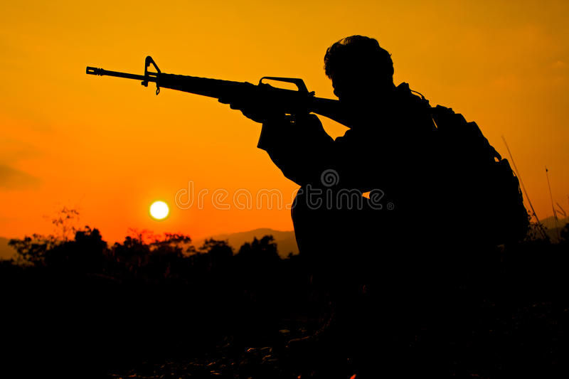 Soldier and gun in silhouette shot stock photo