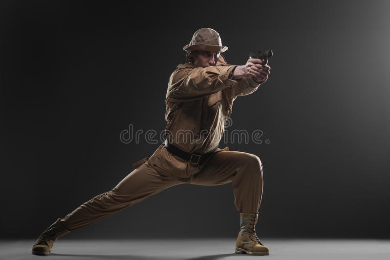 Soldier with a gun takes aim on dark background royalty free stock photography