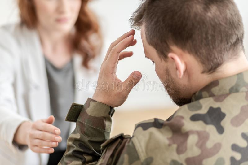 Soldier with headache wearing green moro uniform during meeting with psychotherapist royalty free stock images