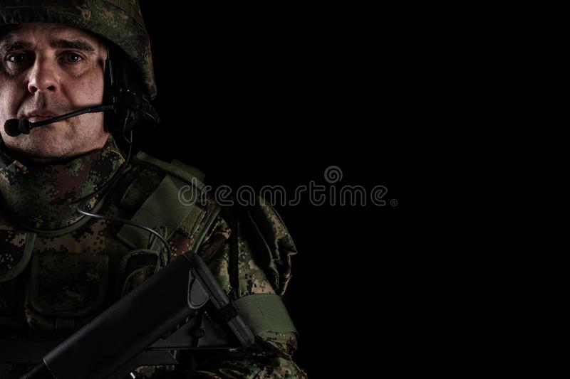 Soldier in the helmet on the black background. Young Soldier in the helmet on the black background royalty free stock image