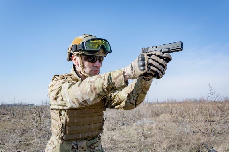 Soldier in helmet with hand gun stock photo