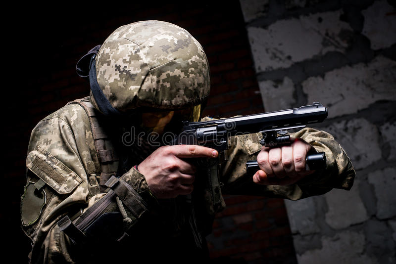 Soldier in helmet and tactical mask on the face with gun royalty free stock image