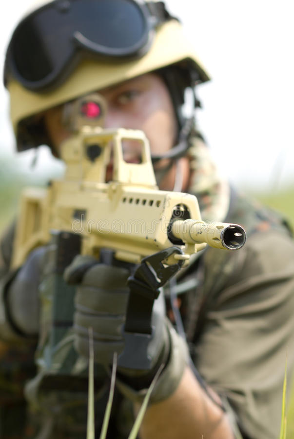 Soldier in helmet targeting with a rifle stock photography