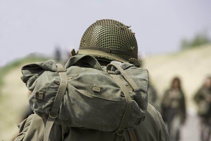 Soldier with helmet. Walking between people royalty free stock image