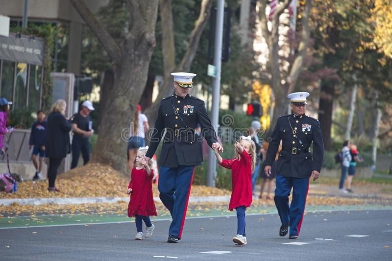 A soldier and his daughters. Veterans Day Parade. Sacramento, California, United States - November 11, 2019: Veterans Day Parade. A soldier walks in the parade royalty free stock images