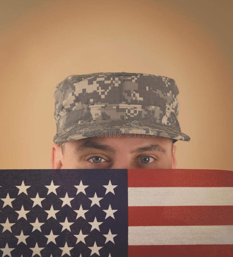 Soldier Holding American Flag to Face royalty free stock photo