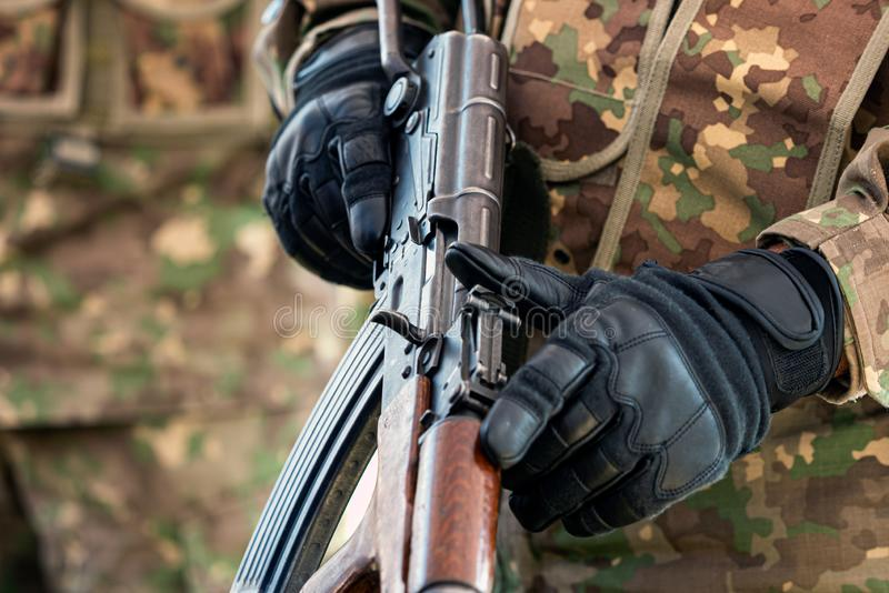Soldier holding automatic weapon in hand ready to fire stock images